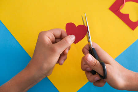 Paper crafts for kids. Child hands cutting colored paper with scissors at the table. Top view