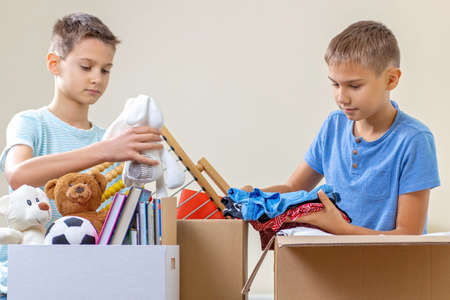 Kids volunteers sorting toys, clothes, books, donation goods in donate charity boxes