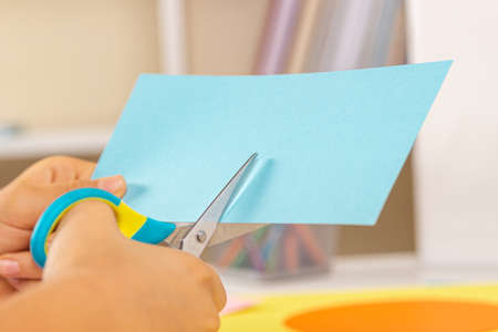 Kid hands cutting light blue colored paper with scissors. Education, learning, paper craft, entertainment