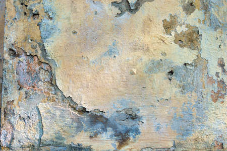 Old cracked weathered painted wall background texture. Light peeled plaster wall with falling off flakes of paint Stockfoto