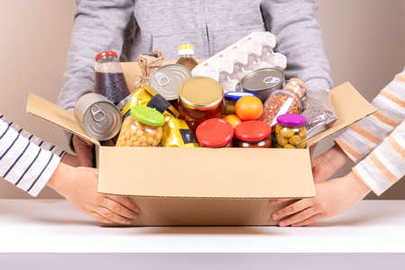 Volunteers hands holding food donations box with grocery products on white desk Reklamní fotografie