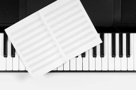 Music learning background. Piano keyboard and music sheet notebook. Top view