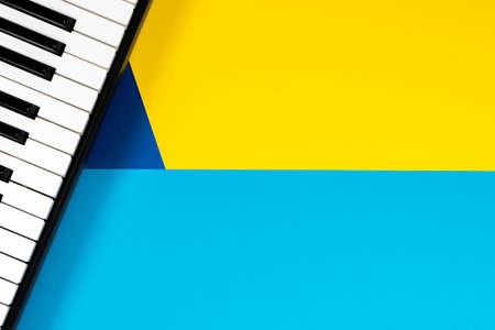 Top view to piano on yellow and blue background. Music learning concept. Top view Reklamní fotografie