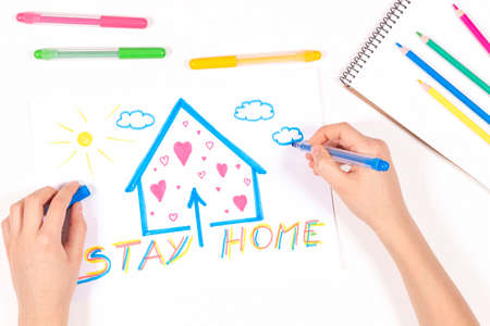 Stay at home. Kid hands drawing picture with house and message Stay home. Top view. Quarantine during coronavirus pandemic Reklamní fotografie
