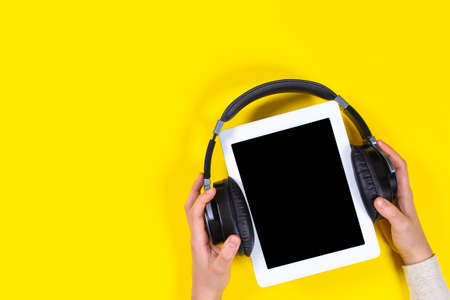 Online learning, remote education, e-learning concept. Kid hands holding digital tablet with wireless headphones over yellow background. Top view Stock Photo