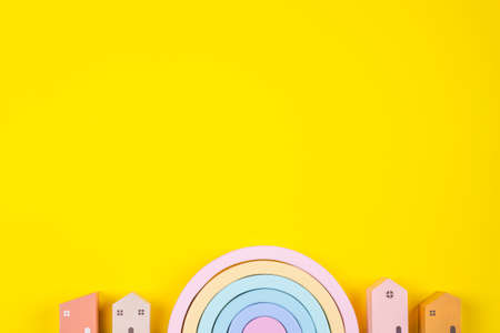 Wooden toys rainbow and colorful houses on yellow background Stock Photo