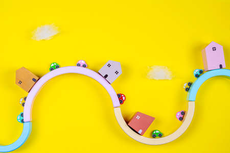 Kid toys background with wooden houses and colorful cars