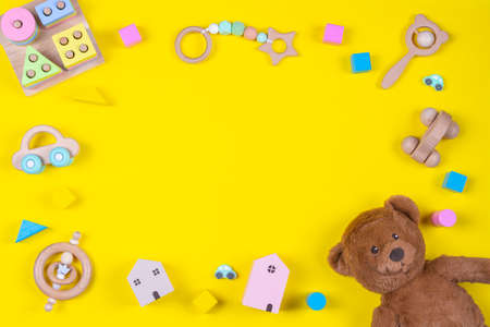 Baby kids toys frame on yellow background. Top view. Flat lay. Copy space for text