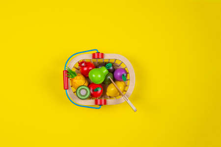 Wooden toy fruits and vegetables in the basket on yellow background. Healthy food. Top view Stock Photo