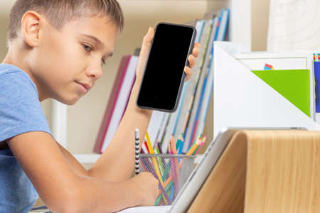 Online learning at home. Boy holding smartphone, looking to digital tablet computer and writing notes or homework