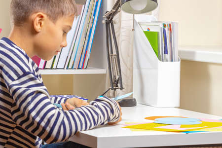 Education, learning, paper craft, entertainment. Boy cuts colored paper with scissors and making craft project at home Stock Photo