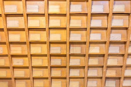Old vintage file catalog box with many wooden index drawers in library archive Stock Photo