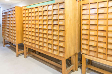Old vintage file catalog boxes with many wooden index drawers in library archive Stock Photo