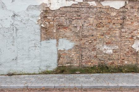 Urban street background. Old grunge obsolete brick wall and pavement