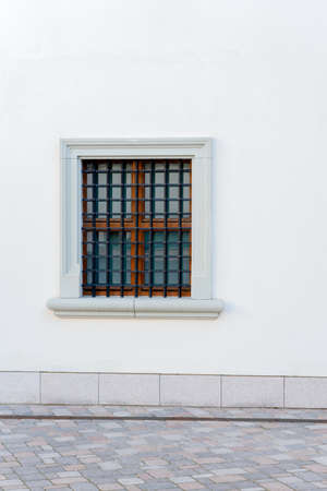 Urban background. White wall with small window and iron grate Stock Photo