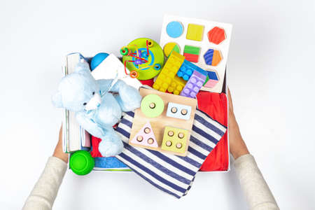 Donation charity concept. Hands holding donate box with clothes, books, school supplies and toys on white background