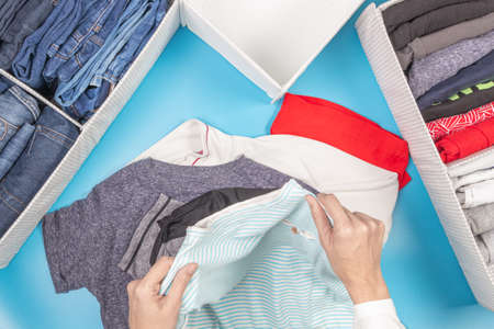 Female hands folds and puts clothes to baskets. Vertical storage of clothing, tidying up, room cleaning. Marie Kondo style of garments declutter and sorting. Top view