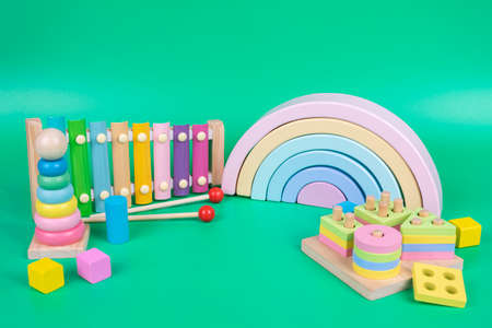 Kids toys collection. Wooden rainbow, educational and music baby toys on light green background Stock Photo