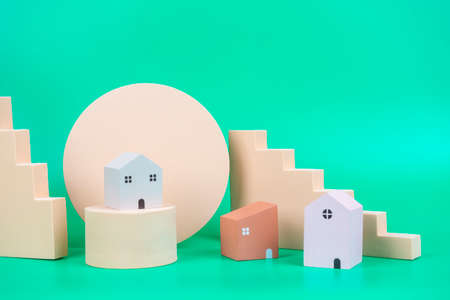 Small wooden houses and geometric pastel color display podiums and shapes on light green background
