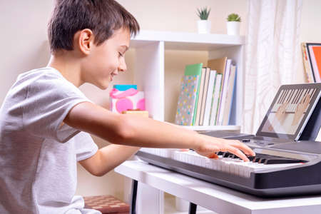 Online learning, remote education. Boy watching video at digital tablet computer and having fun playing piano and singing at home Stock Photo
