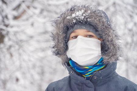 Kid boy wearing medical protective mask having fun outdoors. Active winter leisure, entertainment during corona virus pandemic lockdown Stock Photo