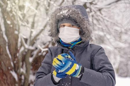 Kid boy wearing medical protective mask playing snowball. Active winter leisure, entertainment during corona virus pandemic lockdown outdoors