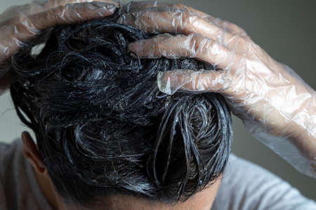 Closeup woman hands dyeing hair. Middle age woman colouring dark hair with gray roots at home