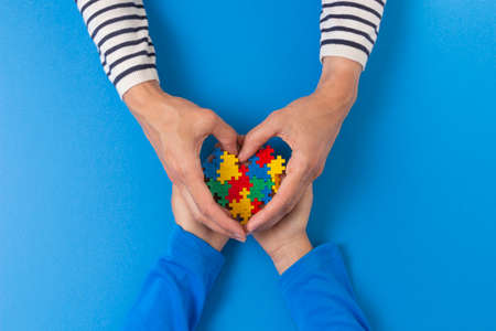 World autism awareness day concept. Female and child hands holding puzzle heart on light blue background