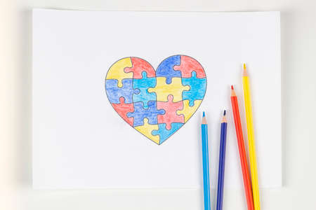 World autism awareness day concept. Puzzle heart colored with pencils on sheet of paper. Top view