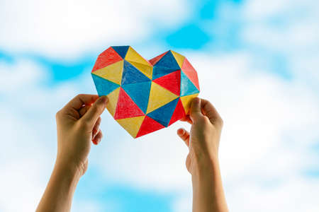 Child hands holding colorful heart over blue sky background. World autism awareness day concept