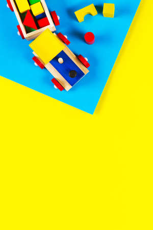 Baby kid toys background. Wooden toy train with colorful blocks on light blue and yellow background. Top view