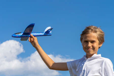 Boy playing with blue toy plane against blue sky at sunny day