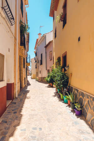 Finestrat, Alicante province, Spain. Beautiful quiet narrow street of small Finestrat village old town at sunny day