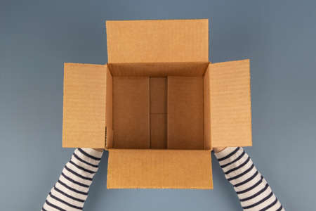 Female hands with empty open cardboard box on gray background. Top view
