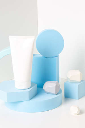 Abstract background trendy composition with one blank cosmetic tube and light blue geometric shapes form podium, platform for product presentation on white background 免版税图像