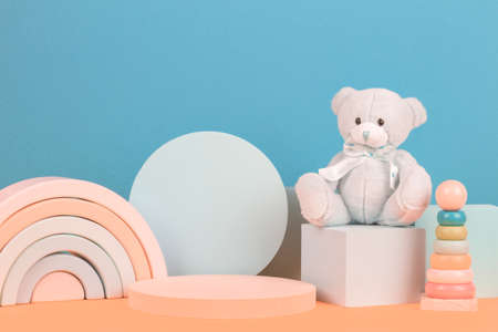 Baby kid toy background. Colorful wooden toys, teddy bear and geometric shapes podium platform with multi colored background