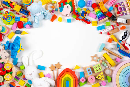 Baby kids toys frame. Set of colorful educational wooden and fluffy toys on white background. Top view, flat lay