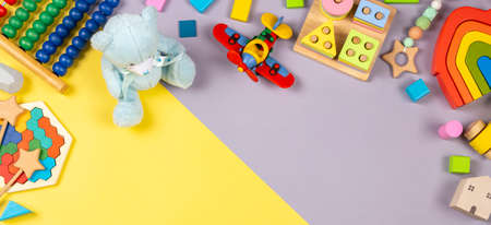 Baby kids toys frame. Colorful educational wooden plastic and fluffy toys for children on yellow and grey background. Top view, flat lay