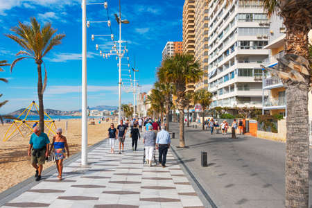 Benidorm, Spain - February 25, 2020: People enjoy sunny day at Levante beach in popular spanish resort Benidorm, Alicante, Spain 新闻类图片