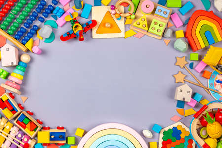 Baby kids toys frame. Colorful educational wooden plastic and fluffy toys for children on gray background. Top view, flat lay