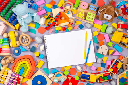 Colorful educational wooden plastic and fluffy baby kids toys and blank notebook with colored pencils on gray background. Top view Banque d'images