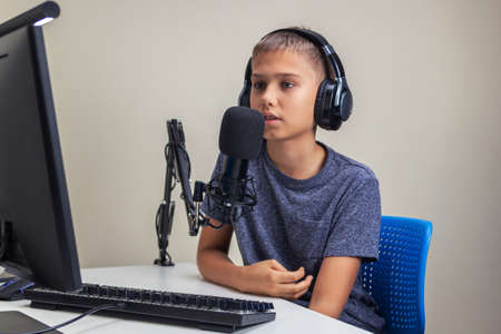 Online learning, remote education, gaming, school concept. Teenage boy wearing headphones using microphone playing video games online on computer, recording podcast, online learning from home