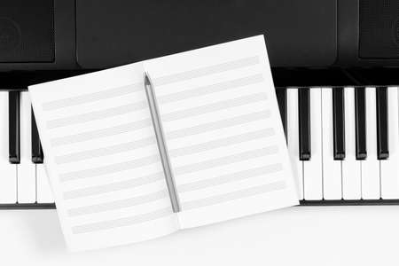 Music learning background. Piano keyboard and open blank sheet music notebook. Top view 免版税图像