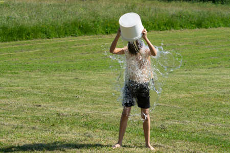 Teenage boy pouring bucket of cold water over his head outdoors. Ice water challenge. Cold water therapy benefits