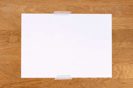 Blank white paper page note stick on wooden background with gray sticky tape