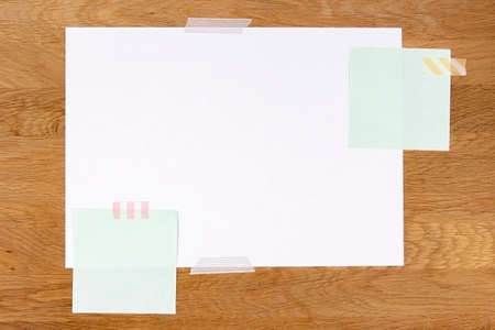 Blank white paper page and note sticks attached with adhesive tape on wooden background