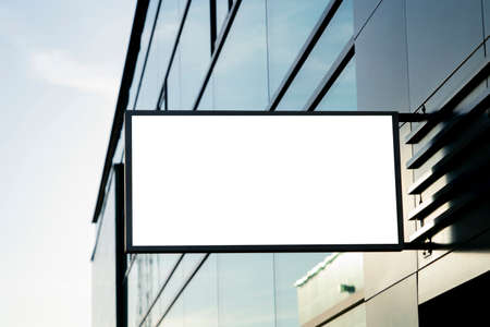 Blank white rectangular mock up street signboard of store, restaurant, office on gray wall outdoors