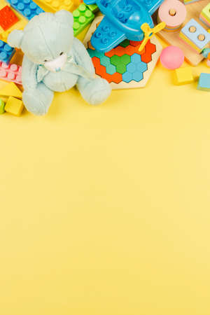 Colorful educational wooden plastic and fluffy toys for children on pastel yellow background. Top view, flat lay 免版税图像