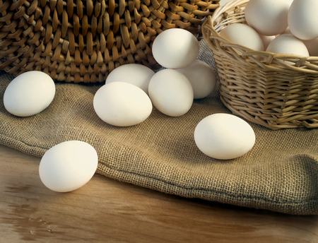A few fresh white chicken eggs in a basket on a burlap over a wooden background