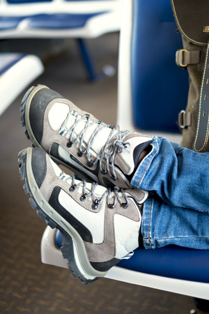 messy clothes: Gray travel boots and khaki camping backpack in a train